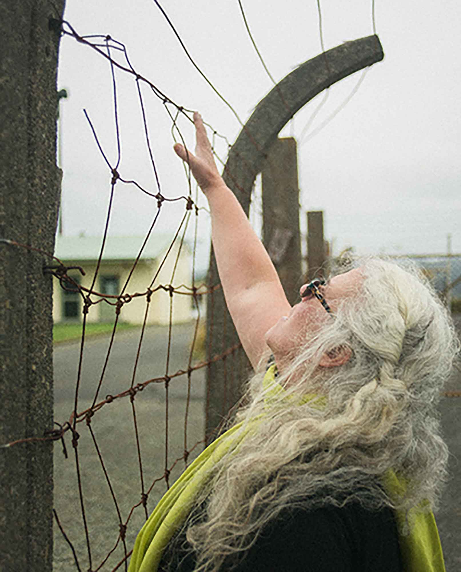 Reading the metal fence surrounding the quarantine station as a sound-text. A still image from performance documentation of windwoundweatherwirewovenwoman (2017). Joshua Lewis photographer.